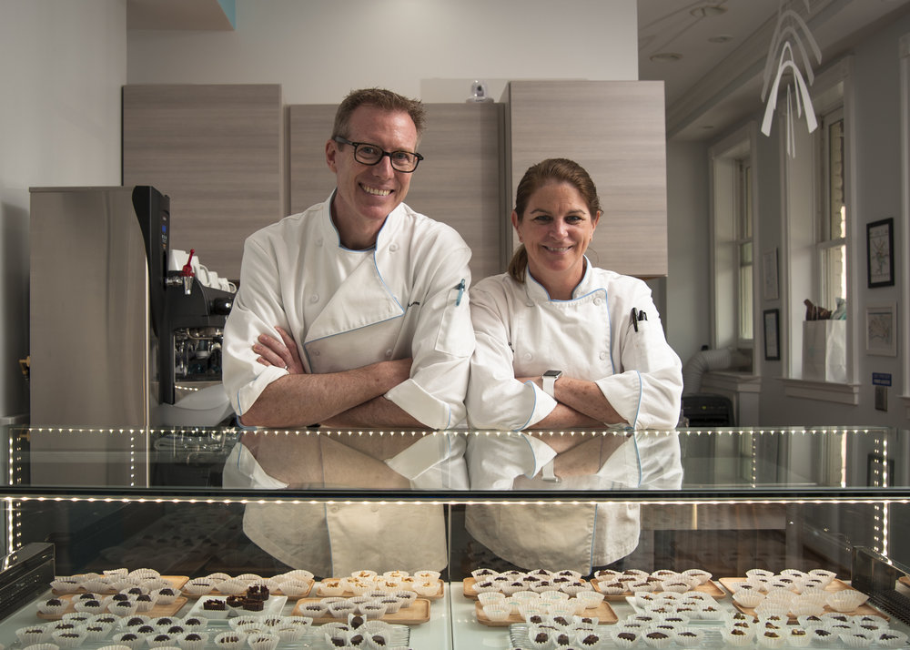 Meet Kim and Bruce Gustafson - We are artisan chocolatiers living and working in Old Town, Alexandria, across the river from the nation's capital. Our retail studio, at the corner of N. Patrick and King Street, is in a hundred-year-old building that was rehabbed in 2005.We create all our pieces onsite, with production downstairs and our retail shop upstairs. And while our specialties are truffles, bonbons and chocolates in delightfully complex and sometimes whimsical flavors (solo, or gift boxed in trios, sixes, sixteens and twenty-fours), we welcome you to stop by for an espresso, coffee, tea or drinking chocolate and rest a moment in our micro-cafe.To complement our own designs, we carry a few select bean-to-bar products from chocolate makers that embrace our unique philosophy: chocolate as form, function, and deliciously fine art meant to seduce all the senses at once. Oh, and for those that crave a little something familiar (yet exotic), we carry chocolate-coated somethings that remind us we are all only mostly grown up, and that chocolate will always be a treat for those that have been especially good!
