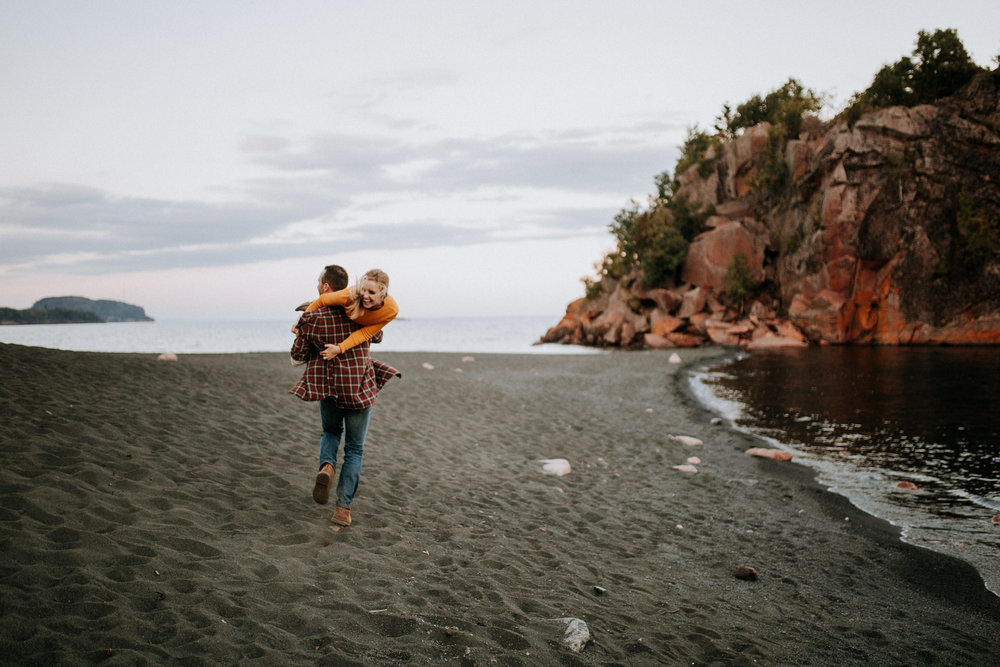 Guy carrying fiancé on the beach in minnesota