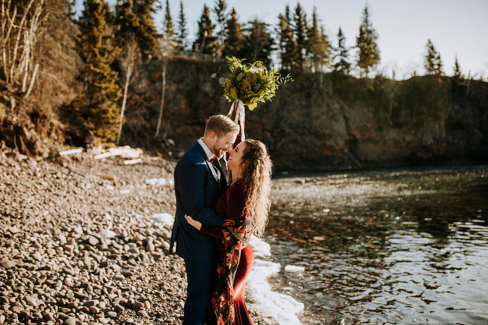 Minnesota elopement on Lake Superior, bride wearing red dress and groom wearing blue suite.