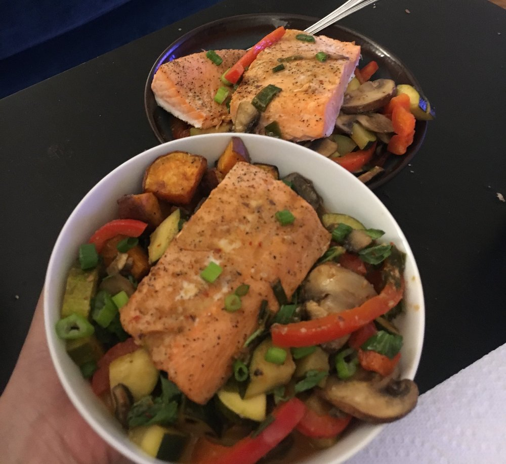 Salmon paired with roasted sweet potatoes and vegetable red curry. Mine in the front (4 oz salmon) and my boyfriend's in the back (8 oz salmon).