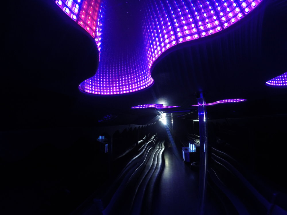 Purple Infinity Lights on Stunning Shiny Black Seating in Liberty Bus