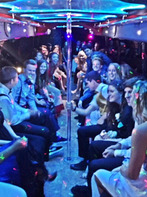 formal wear kids on the way to graduation in a limo bus with friends.jpg