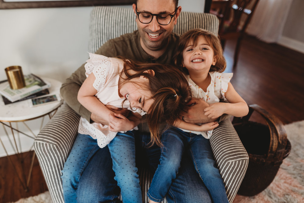 dad laughing with daughters