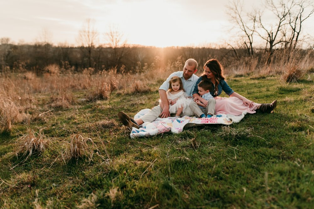 family snuggling in field STL Photographer