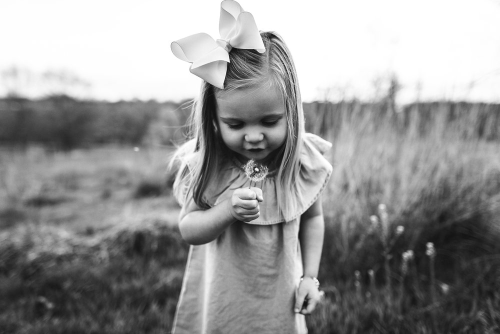 girl blowing flower