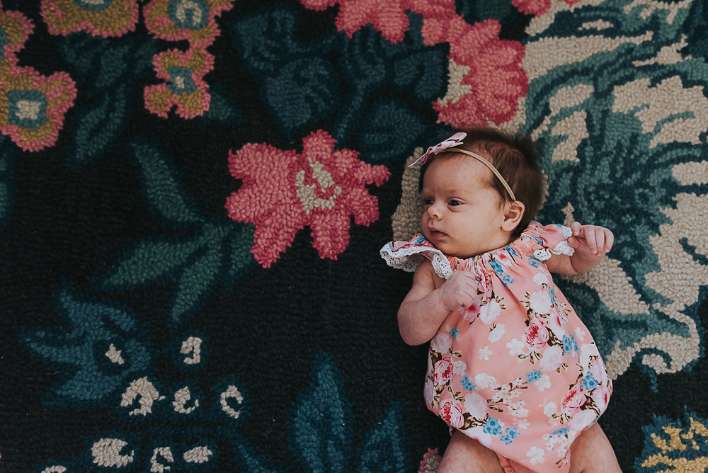 newborn baby girl on floral rug