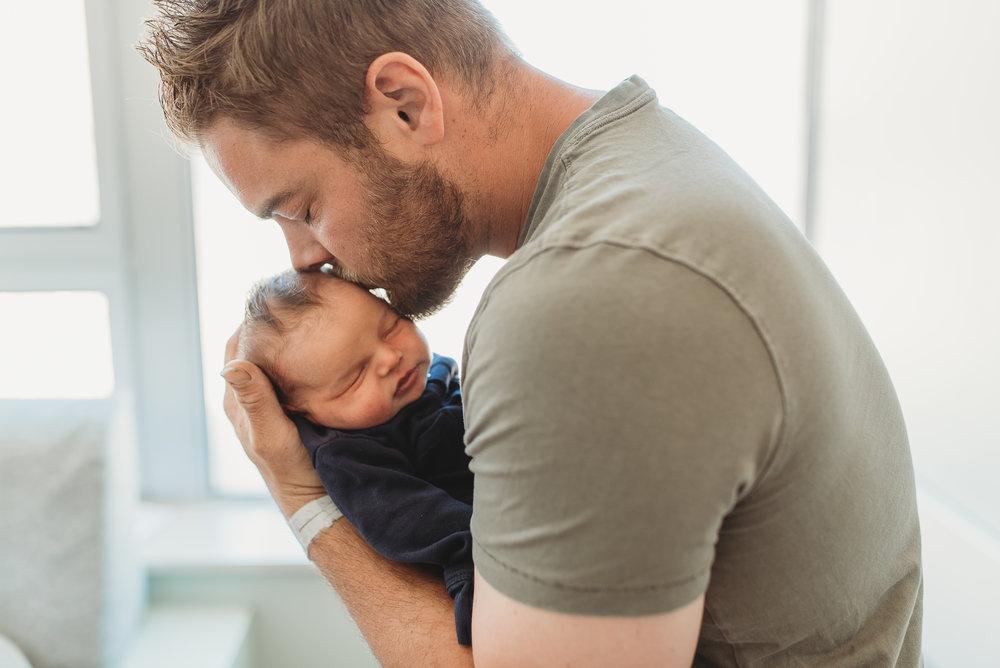 new dad kissing newborn