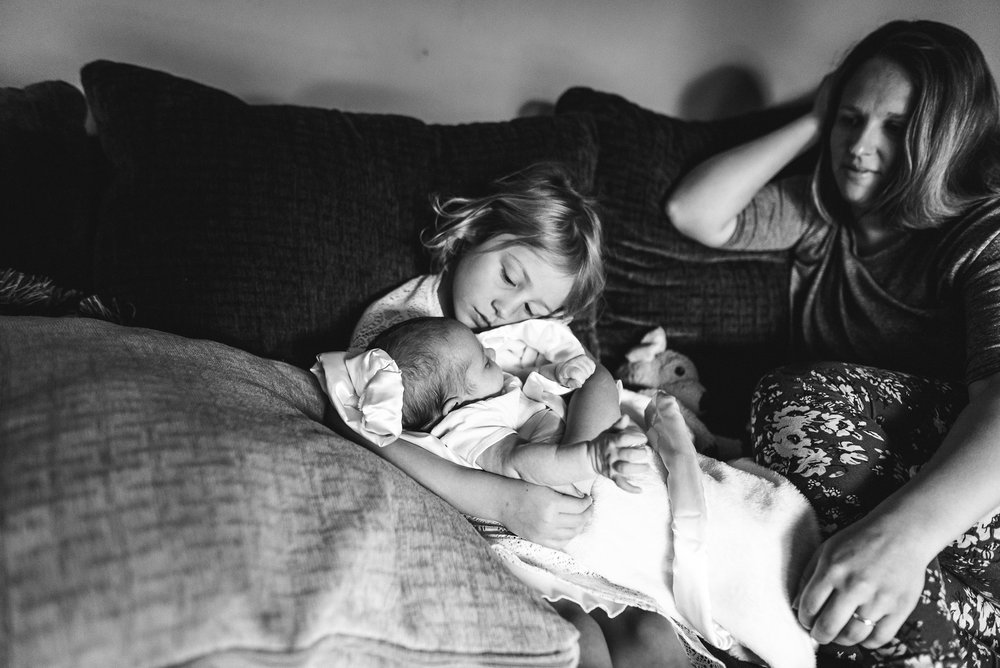 mom watching daughter hold new sister