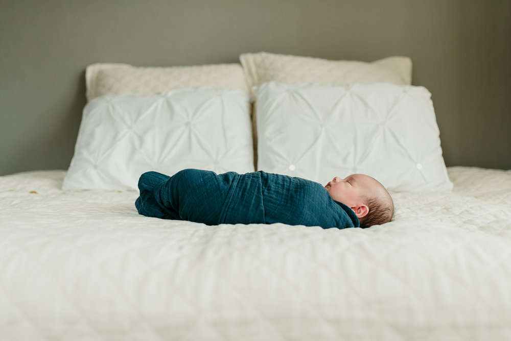 baby sleeping on parent's bed