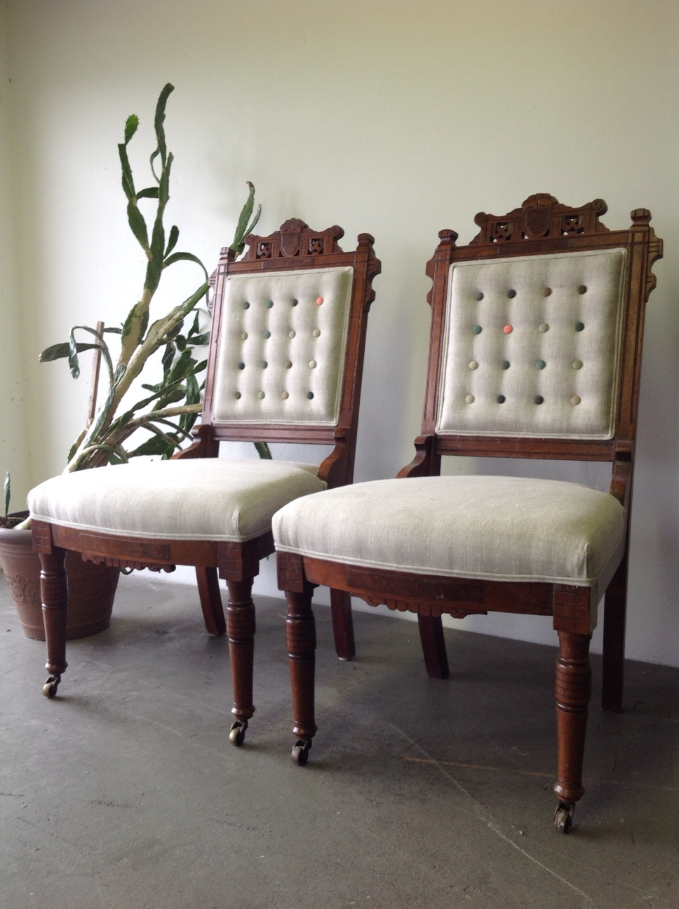 Antique Eastlake dining chairs upholstered in linen, with multi-coloured shallow button tufting and double piping trim.