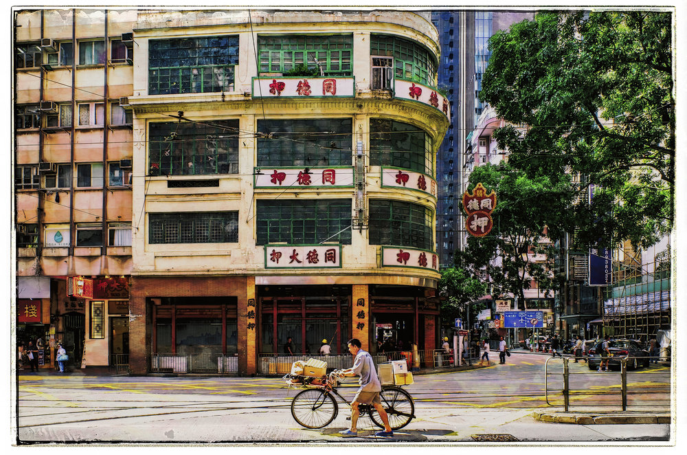 Pawn Shop or Hidden Gem?    I love photographing local pawn shops in Hong Kong and Macau.    Here's an example of what I am talking about. What is that building over there? The simple answer is: That's a pawn shop. You go there and borrow money against personal property such as jewelry placed on deposit. The red sign denotes an upside down bat with a coin in it's mouth and involves a fair amount of Cantonese wordplay.    Is that a hidden gem? Well, when you consider there are pawn shops all around Hong Kong. Not really hidden are they?    What if I were to tell you the pawn shop in China dates from the last quarter of the of the 5th Century A.D. That they were originally a commercial enterprise restricted to Buddhist monasteries where they remained for several hundred years. That in the Ching Dynasty there were almost 25,000 of them and during the Sung Dynasty lay proprietors wore black gowns to imitate the black robes of Buddhist monks. Suddenly pawn shops become very interesting indeed. Context adds to the scene above.    BTW, that was the old Tak Shing Pawn Shop on Hennessy Road. After a community fight to preserve it was lost, it was finally torn down by the owner to build another office tower. And don't worry, I won't forget to explain the Cantonese word play on tour.    (Source: The Pawnshop in China, T.S. Whelan, 1979 (Originally Published in Chinese in 1929)