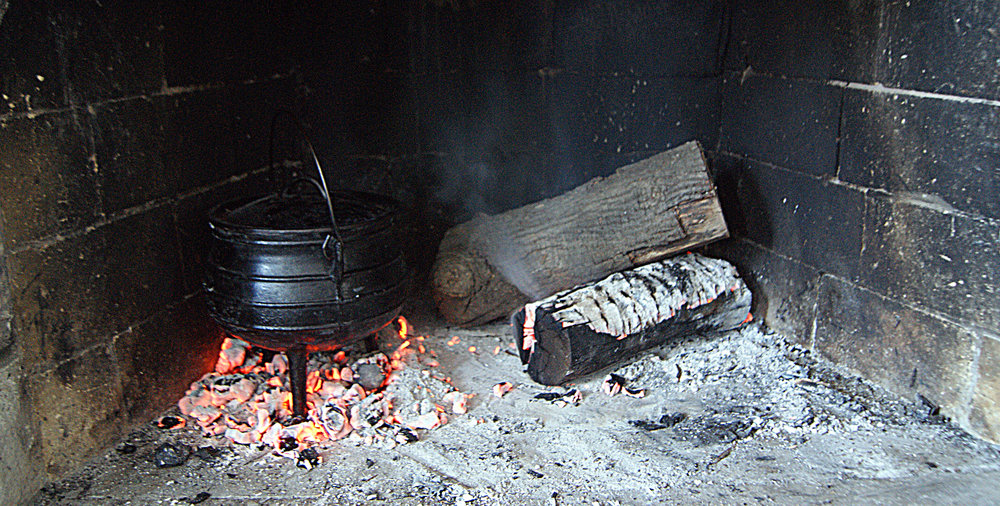 Let the coals do the work for you, place the item to be heated upon the coals, with a trivet if it is missing legs.
