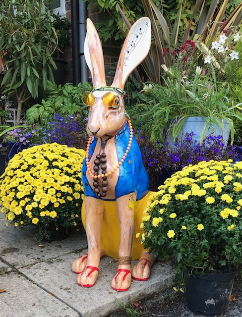 Hare, sitting in the flowers and waiting to hear who won the bid for him