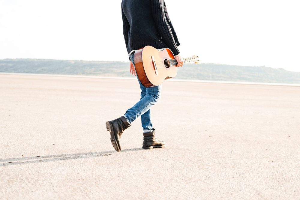graphicstock-cropped-image-of-a-casual-man-holding-guitar-and-walking-across-seashore_Hux4aT_82x.jpg