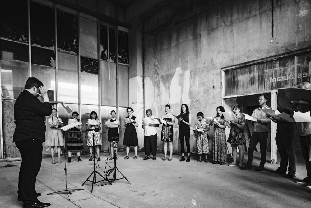 Guest conducting London Metropolitan University's Musarc Choir in  Benjamin Tassie 's 'Silvertown' at the old Carlsberg & Tetley's Factory in  Silvertown , London (UK); June 2017