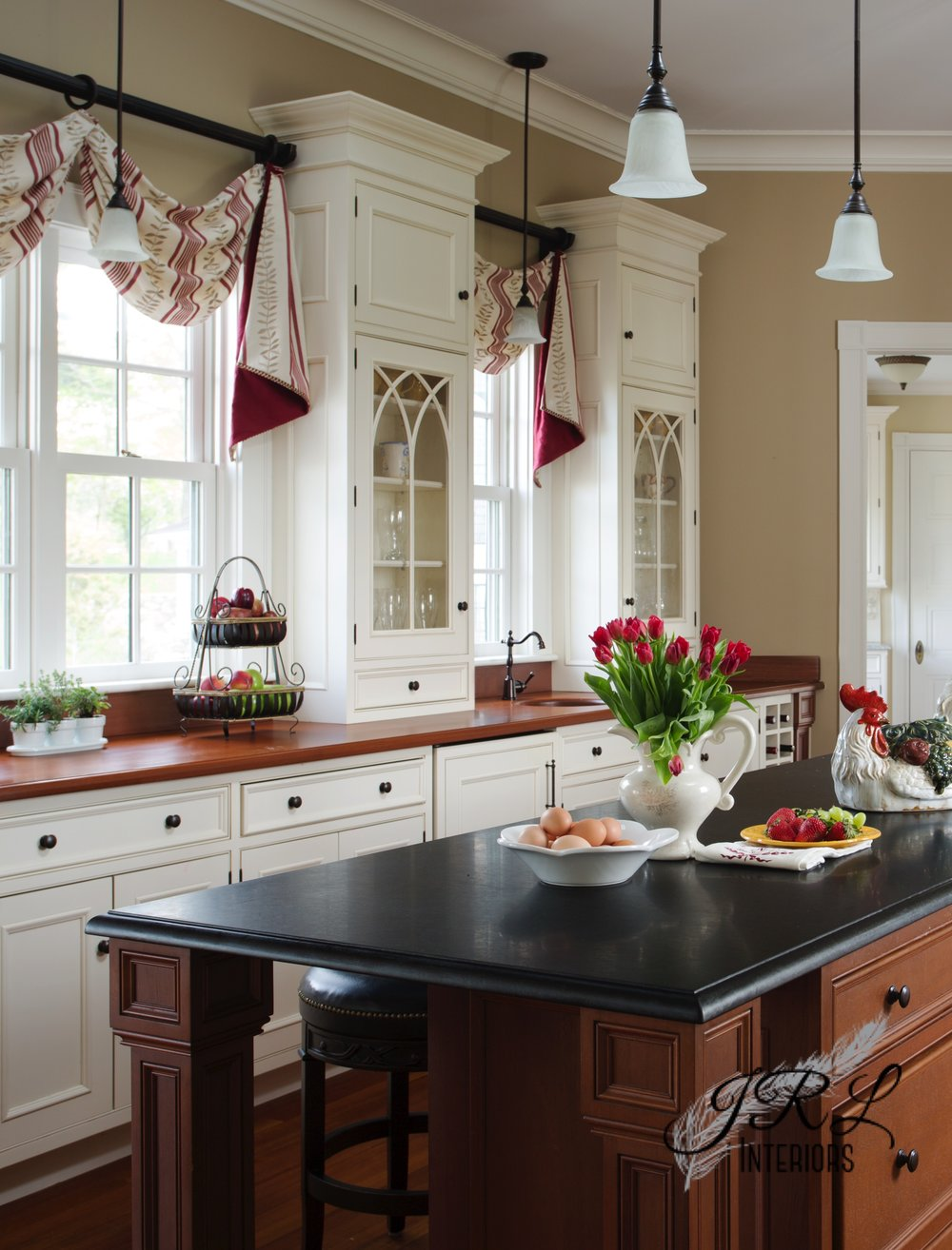 Leather swivel stools with nailhead trim tuck neatly under the island in this elegant farmhouse kitchen when not in use