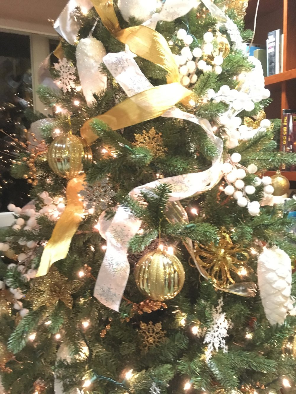 This tree and mantel got treated to a gold, silver and white winter wonderland look with snowflake ribbon and ornaments, gold, silver, and white ornaments in various shapes and sizes, and gold berry sprigs and white snowball berry branches