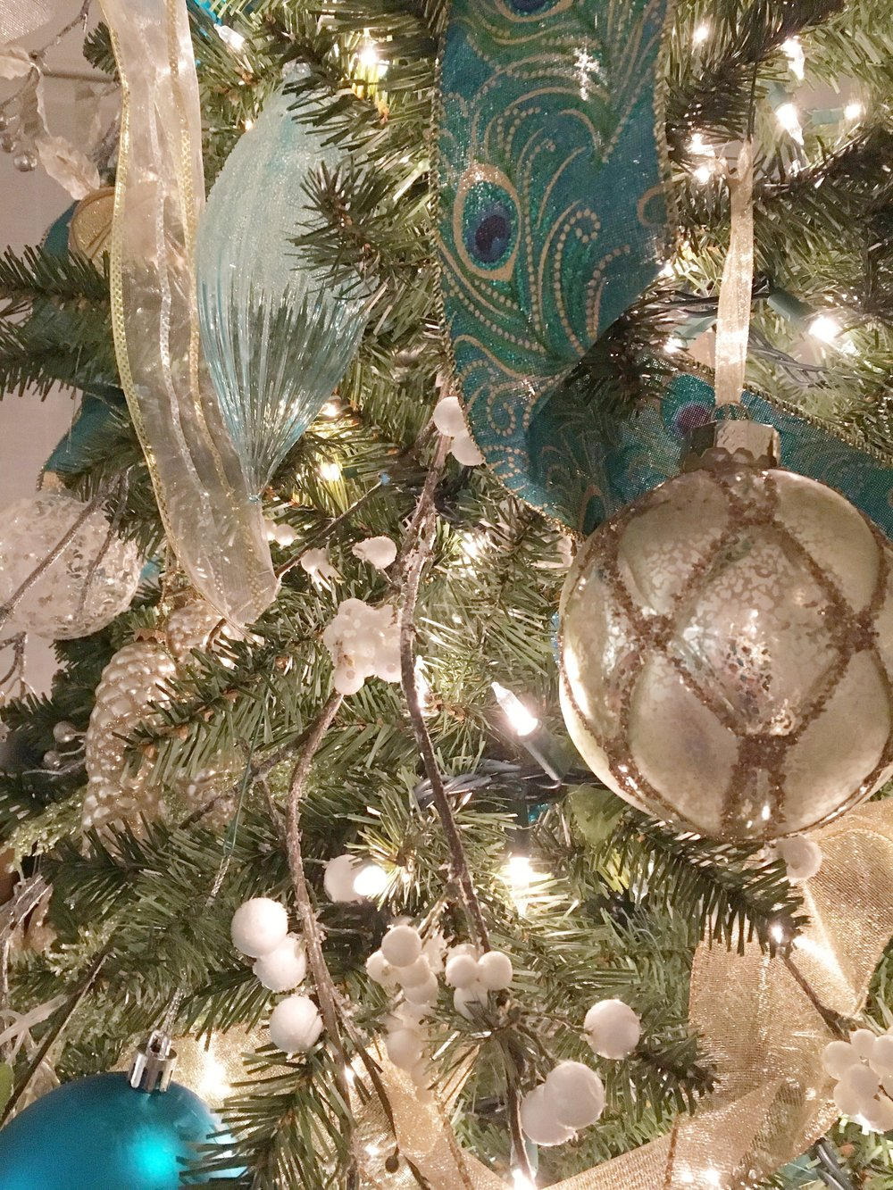 The client's ornaments mixed with new ornaments, berry branches, and an abundance of ribbon make a striking statement tree