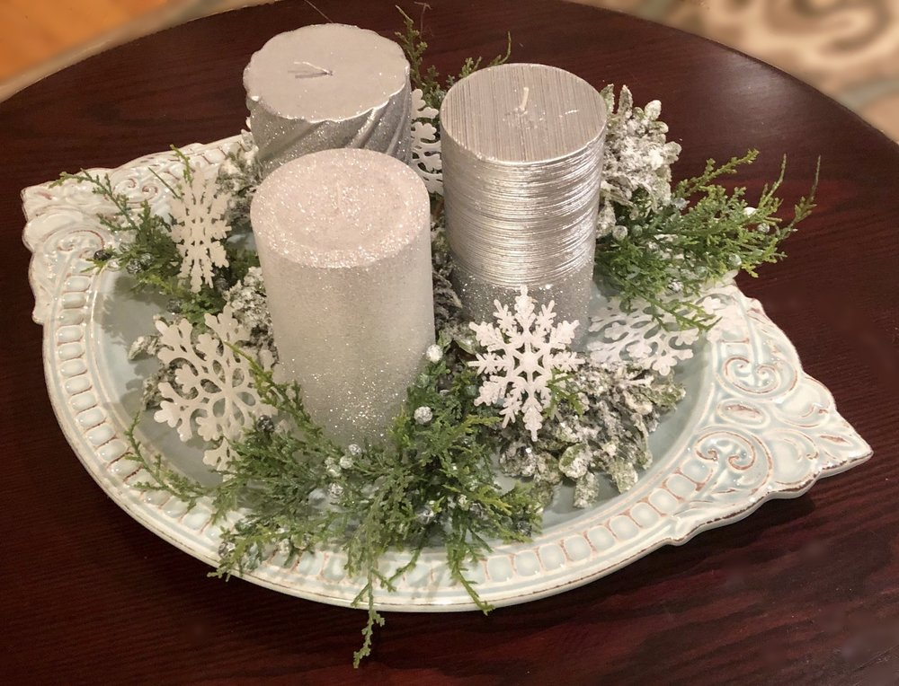 The coffee table was styled with the innkeepers pretty aqua platter filled with a trio of silver candles, mixed greens and white snowflake ornaments