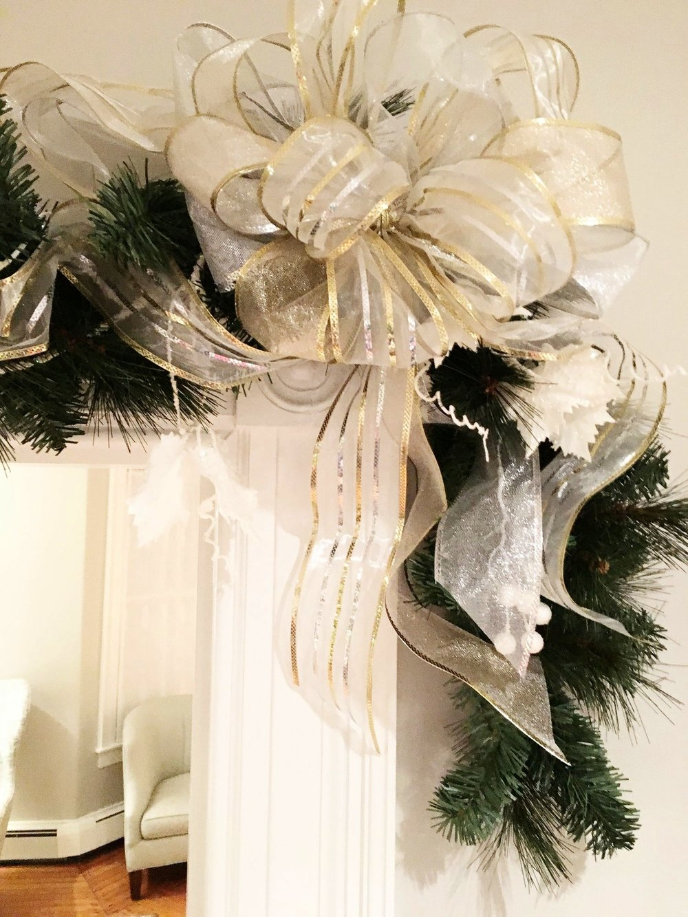 Archway garland with white frosted grapevines and berries and silver and gold bows in the auxiliary dining room