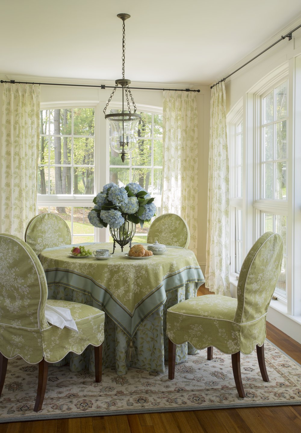 This bell jar fixture is the perfect style for this sunroom corner dining spot.