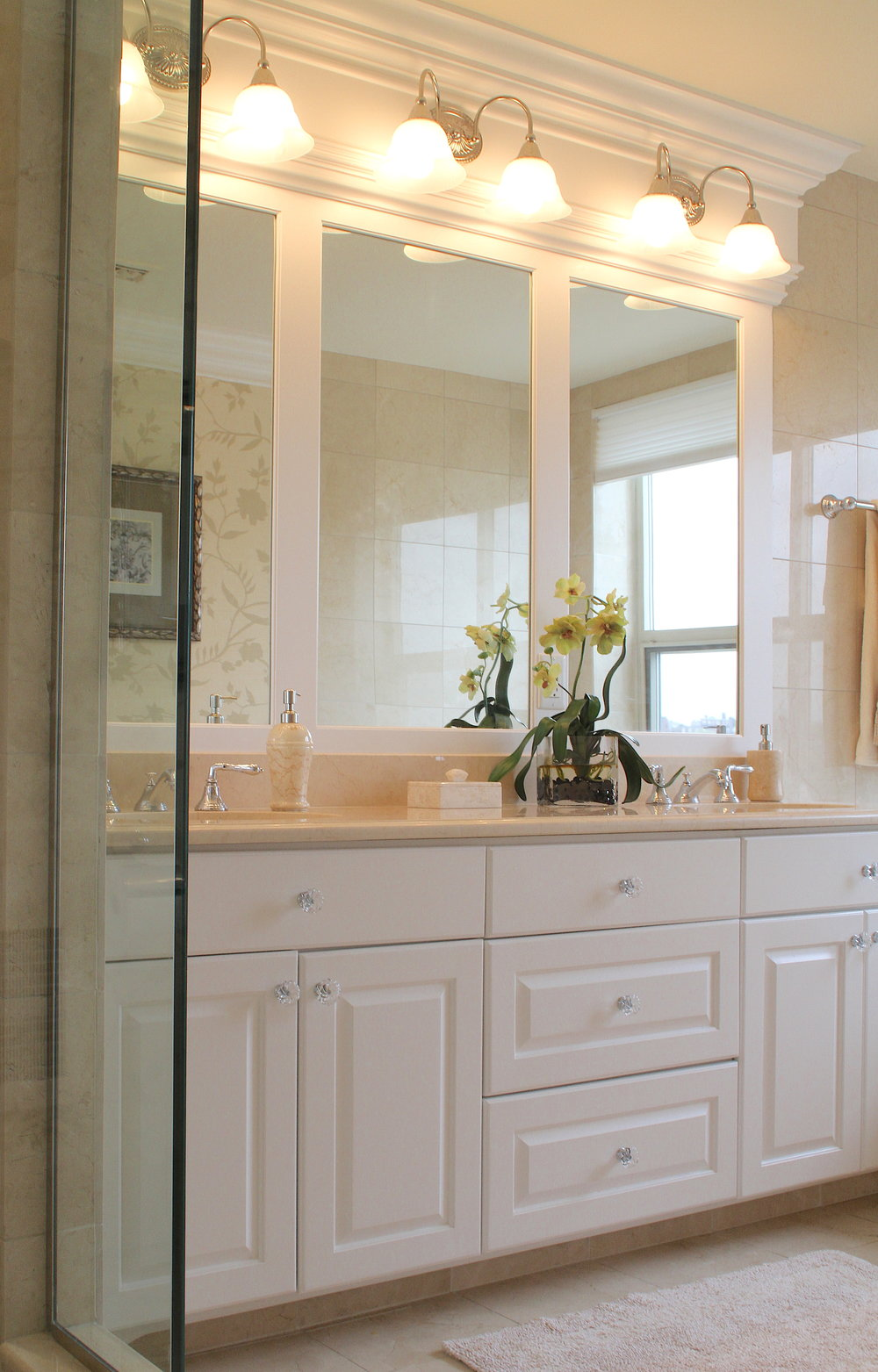 Custom millwork was designed to mount these light fixtures over the mirrors in this master bathroom renovation.