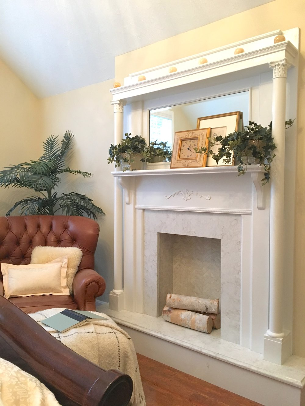 This faux fireplace was built-in to add charm to this master suite. The victorian oak mantelpiece was an item the homeowner had purchased at auction years ago and had never had a place to use. We built out the wall to create a faux chimney breast and raised hearth faced with quartz. The firebox was tiled with coordinating marble-look porcelain in a herringbone pattern.