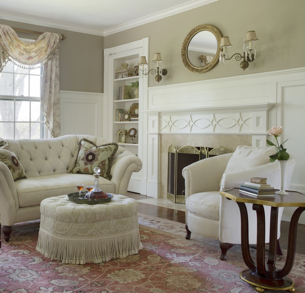 This fireplace, with simple detailing that echoes the leaded glass in an adjacent space, is built into a wall with wainscoting. The very shallow mantel shelf is deliberately left unadorned. A pair of sconces flank a round mirror for a simple symmetrical arrangement.