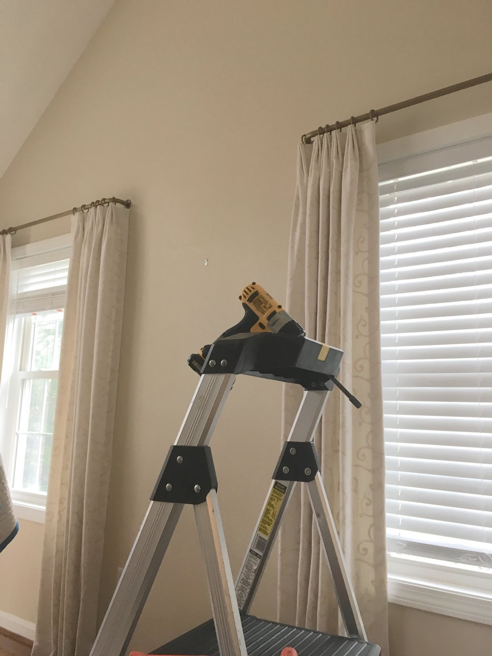 This is one of our drapery installations in progress. For this project we used custom French style rods that curve back to the wall. The rods are wider than the window casing and mounted level with the top of the wall where it meets the vaulted angled ceiling.