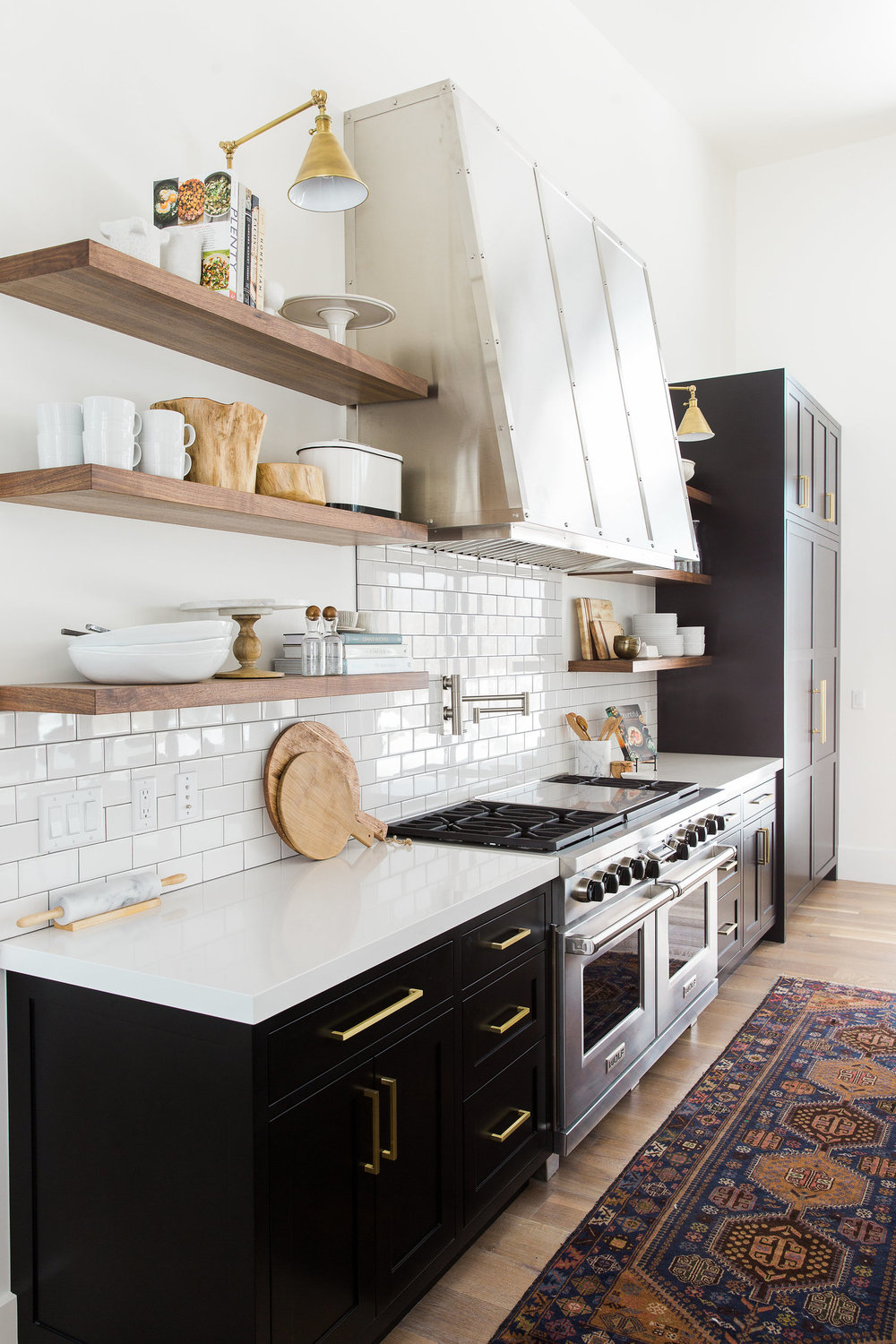 Notice that in this stunning black and white kitchen by   Studio McGee  , how stainless appliances, hood, and faucets are beautifully mixed with brass cabinet hardware and light sconces.