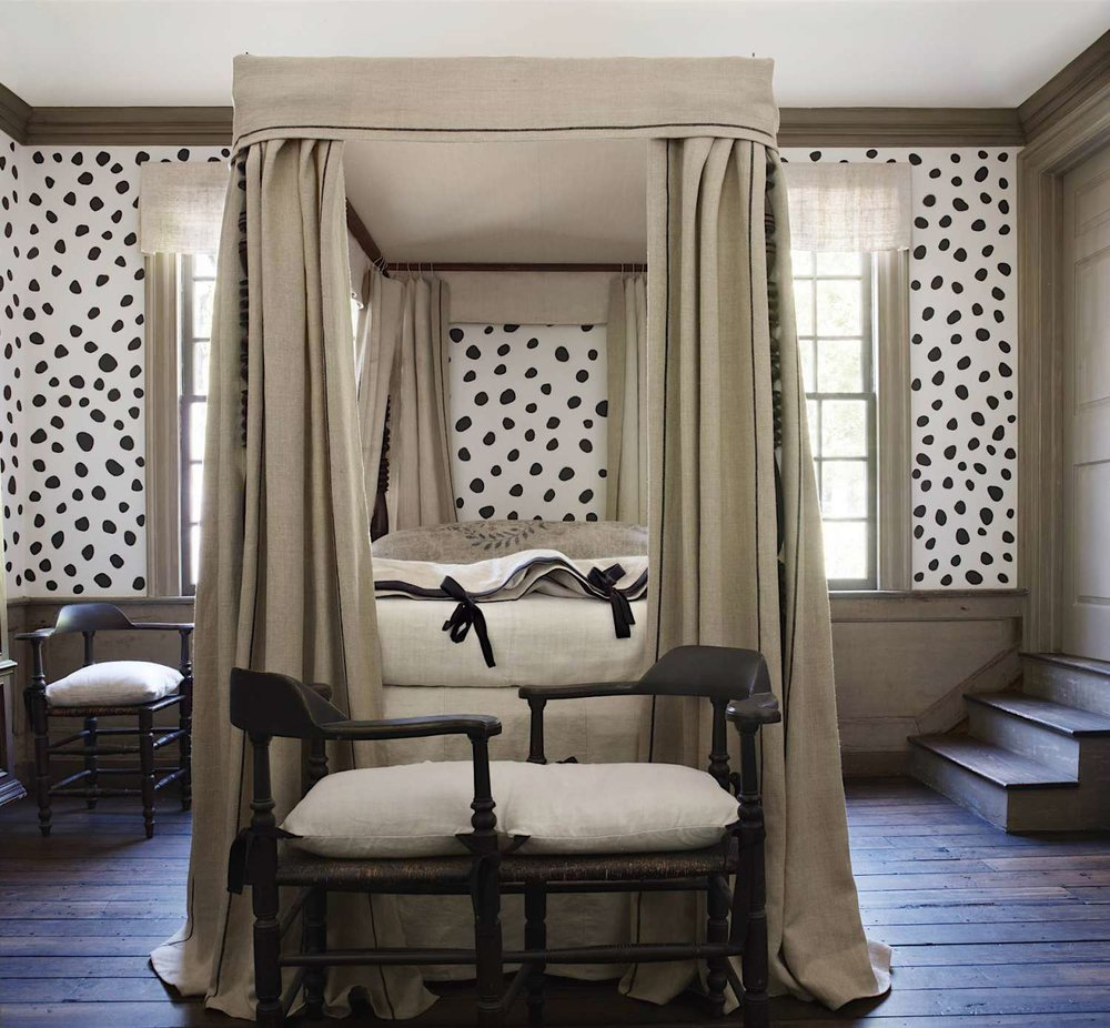 Spotted walls lend a playful energy to this guest room by   Nancy Braithwaite