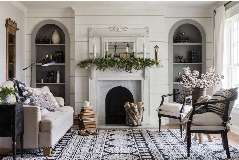 This Magnolia Home (the shiplap was a dead giveaway) area rug in black from   Shades of Light   ,  along with black accents in the drapery hardware, chair frames, lighting, side table and accessories balance the abundance of soft white and gray tones.