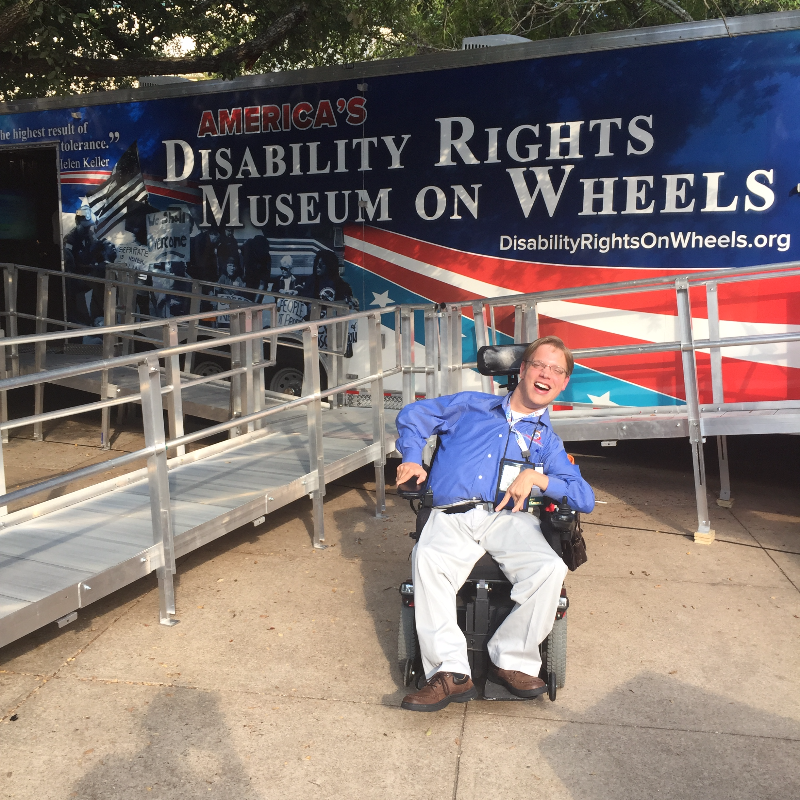 PHOTO: Matthew sitting in front of The Disability Museum on Wheels smiling.  This picture was taken at the 2015 USBLN annual conference in Austin Texas.