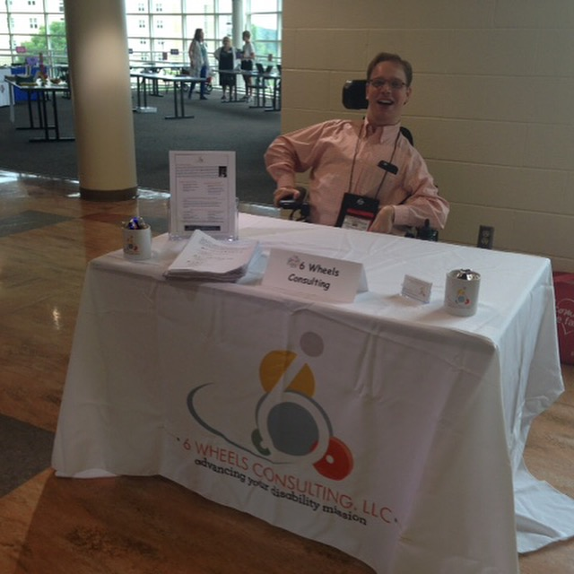 PHOTO: Matthew sitting behind his 6 Wheels Consulting table At the resource fair at the I'm Determined Summit at JMU.