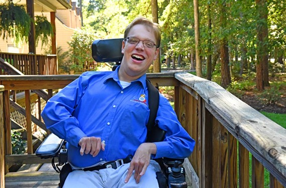 PHOTO: Picture of Matthew in his wheelchair on his ramp and in his 6 Wheels Consulting, LLC shirt.
