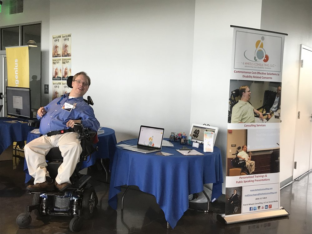 PHOTO: Matthew sitting at at his resource table at 2018 Virginia Venture Summit.