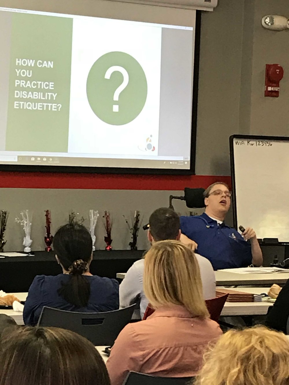 PHOTO: Matthew sitting In front of a screen presenting his disability etiquette training at New Editions Consulting Inc.