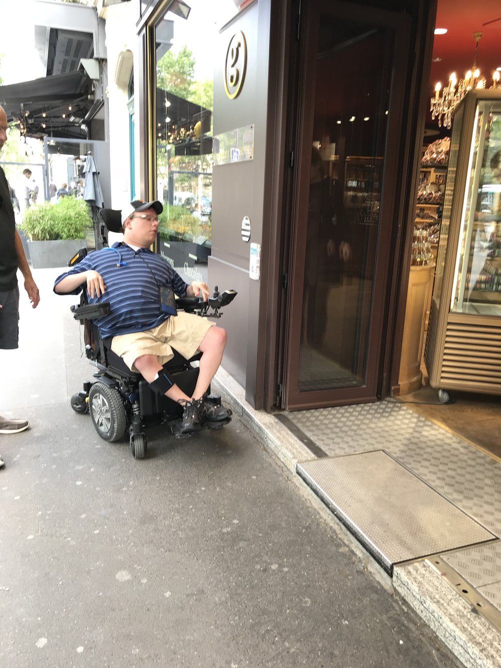 PHOTO: Matthew sitting in his wheelchair in a blue shirt and cap outside a store in Paris, France.  He is looking at a gray platform.