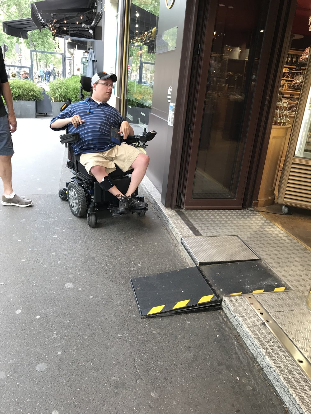 PHOTO: Matthew still sitting in his wheelchair in a blue shirt and cap outside a store in Paris, France.  Now he is looking at a black ramp to help him get in the store.
