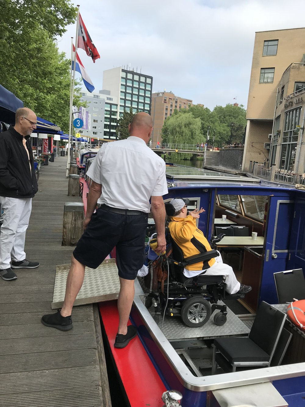 PHOTO: Matthew in his chair, in a yellow shirt, using a lift to get into a canal boat in Amsterdam.