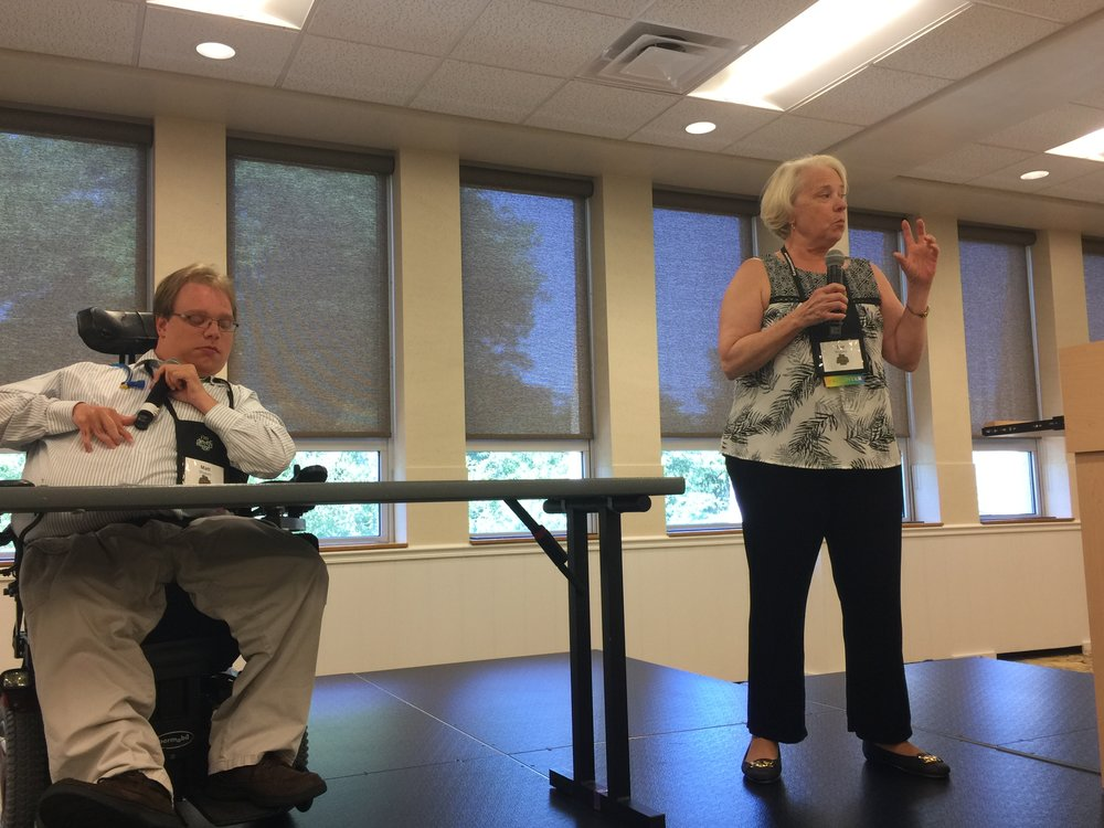 PHOTO: Matthew, sitting behind a table, and his mom, Eve, presenting on the stage at the I'm Determined Parent Summit In Harrisonburg, Virginia at James Madison University.