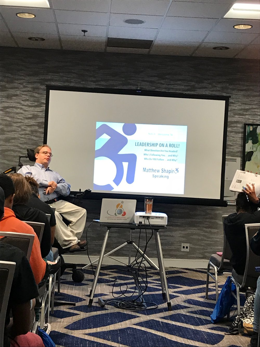 PHOTO: Matthew, sitting in his wheelchair, In khaki pants and a button-down shirt, In front of a projector screen getting ready to begin his Leadership on a roll program in his Ed session Atlanta.