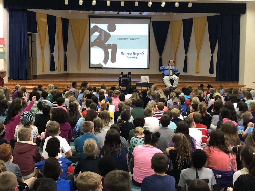 PHOTO: Matthew sitting In front of 250 fourth and fifth grade students Woolridge Elementary School during his Positively Inclusive presentation.