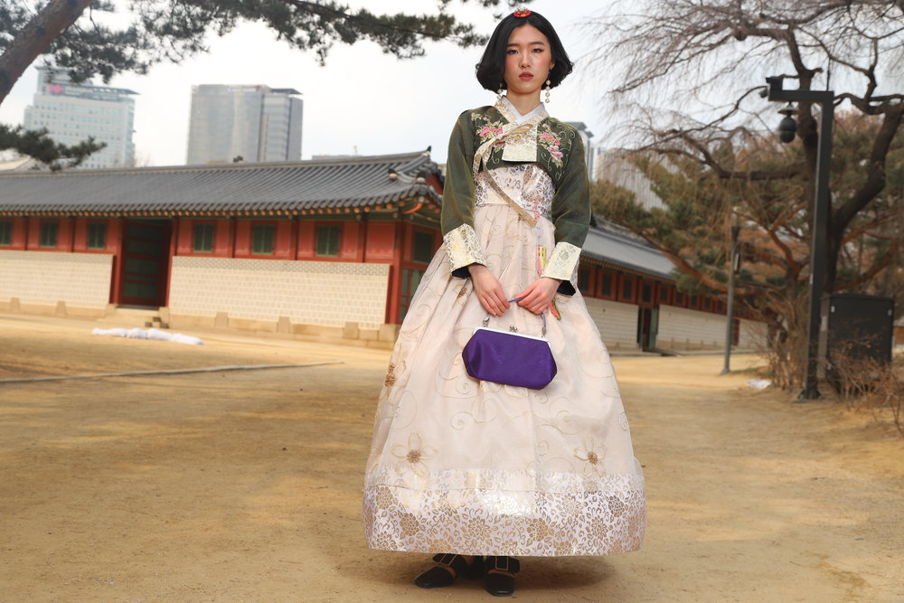 TOURIST Korea, done WRONG. Our model Jihye poses in one of the standard korean hanbok often rented out to tourists, which are considered by many actual hanbok designers an affront to the idea of the original hanbok, made as they are with hoops like found in a western-style ballroom dress and fabrics and patterns that, while pretty, are not even traditional Korean patterns or materials but rather look like those found on window drapes.