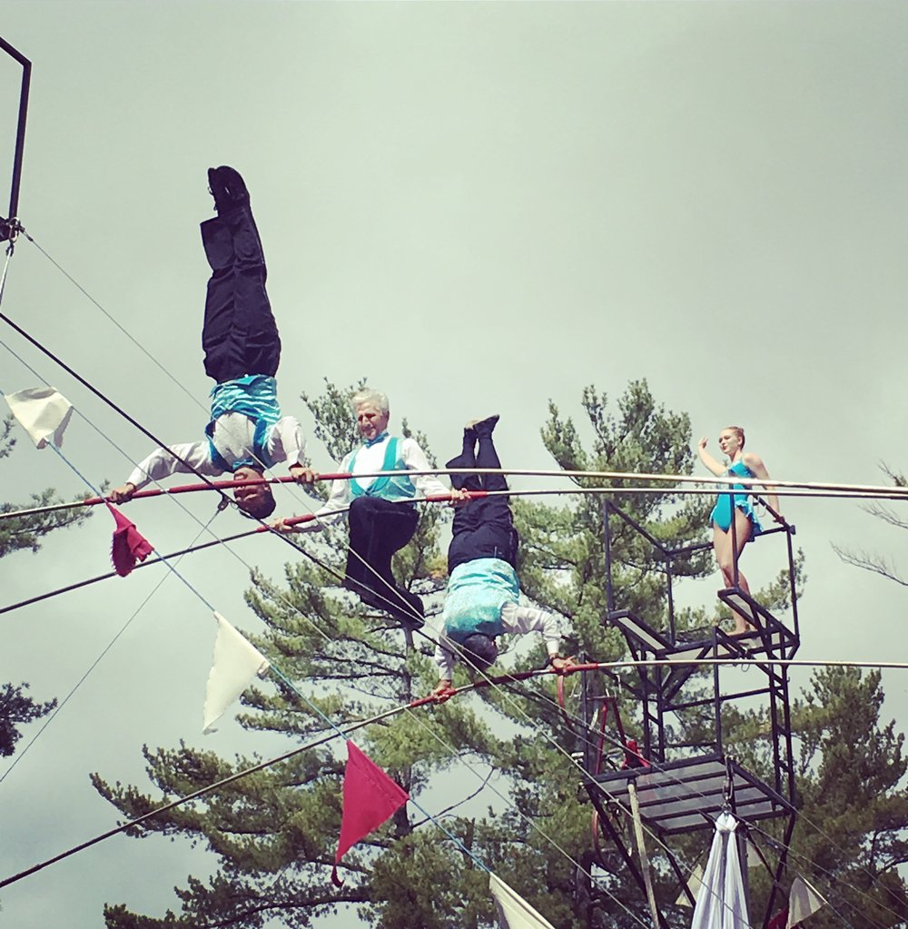 Moody Street Circus CoFounder Sacha Pavlata kneeling on the high wire with Tino and Alex Wallenda at the Deerfield fair.  Zoë Heywood is on the platform.