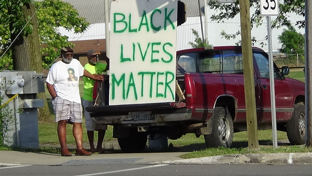 "Erie, PA (July 22, 2016) Men standing outside of their truck with a ""Black Lives Matter"" sign during a peace rally on the corner of East 12th and Wayne Street in Erie, PA. (Photo Credit:  Lauren Benzo )"