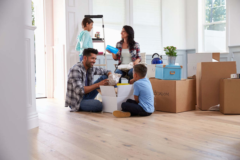 couple and two children  taking stuff out of moving boxes
