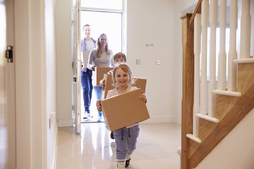 two kids carrying boxes entering new home ahead of parents
