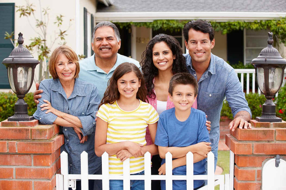 multi-generational family posing behind white picket fence of home