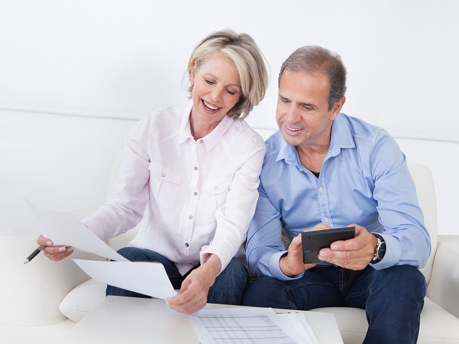 mature couple looking at documents and writing notes on couch